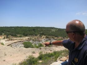 Troy Henderson, with the Brownwood Lake Patrol, shows where erosion has eaten at a dam's spillway.