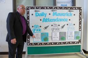 Ron Gonzales points to his Daily Maverick Attendance board, where he posts daily attendance rates for each grade. One of his goals is to increase daily attendance rates at Mendez Middle School, where he's been principal for four years.