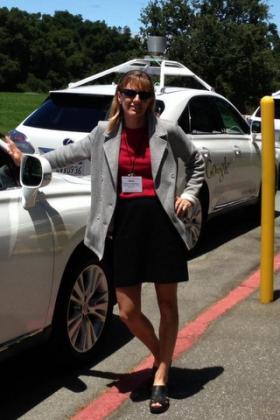 UT Engineering Professor Kara Kockelman, next to a fleet of driverless car prototypes.