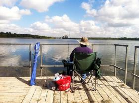 A fisherman sits on the dock on Walter E. Long Lake.