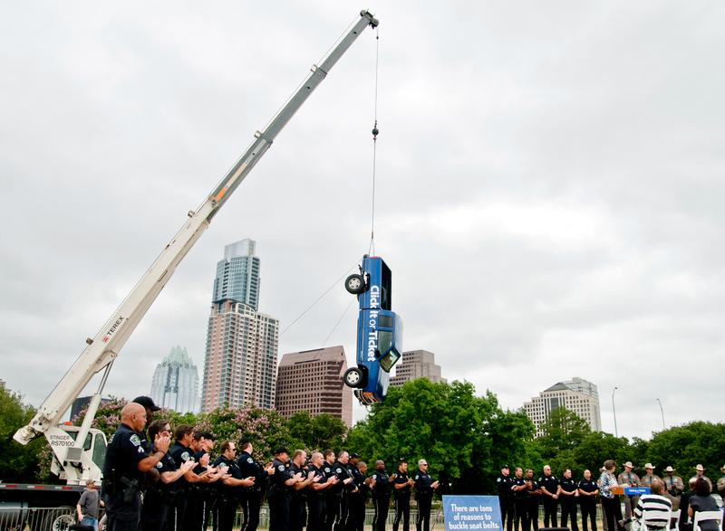 Raising awareness for auto safety, seatbelts were used to hoist a truck in Downtown Austin.