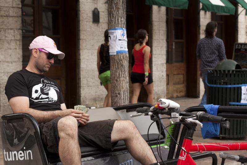 A pedicabber counts his cash during South by Southwest 2012.