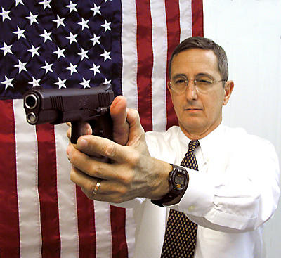 Texas Land Commissioner Jerry Patterson holds a gun in front of an American flag