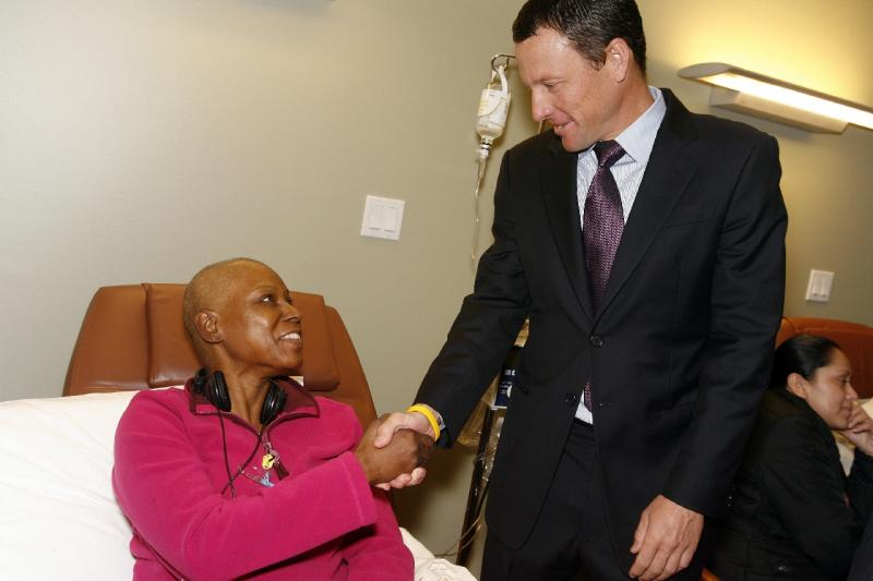 Lance Armstrong greets cancer survivor Marie McKinney.  Armstrong says he is leaving profesionnal cycling to continue his efforts to promote cancer research and raise awareness about the disease.