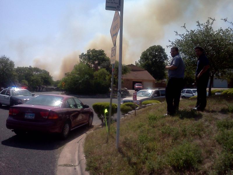 Evacuees try to get out of the way of a brush fire threatening at least one subdivision in the Oak Hill area.