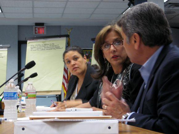 Superintendent Meria Carstarphen (left) speaks with school board members Lori Moya and Vince Torres during tonight's meeting.