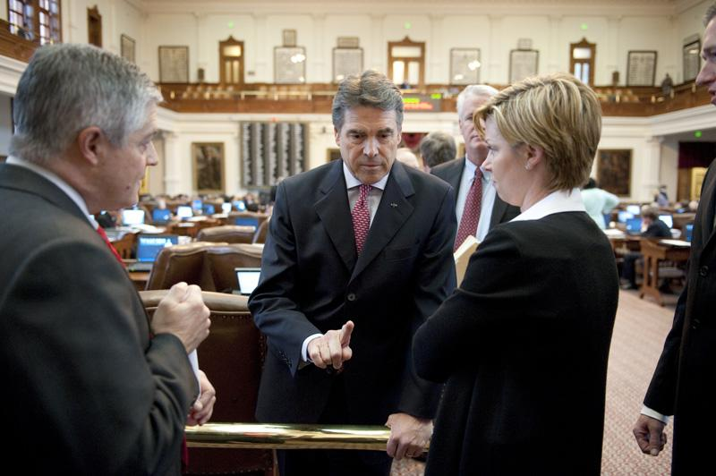 Texas Gov. Rick Perry visits with House members to discuss the state budget issues at the back railing on May 19, 2011.