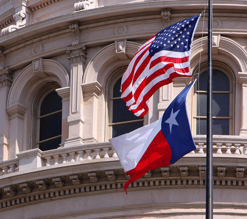 US and Texas flags flutter in front of the State Capitol