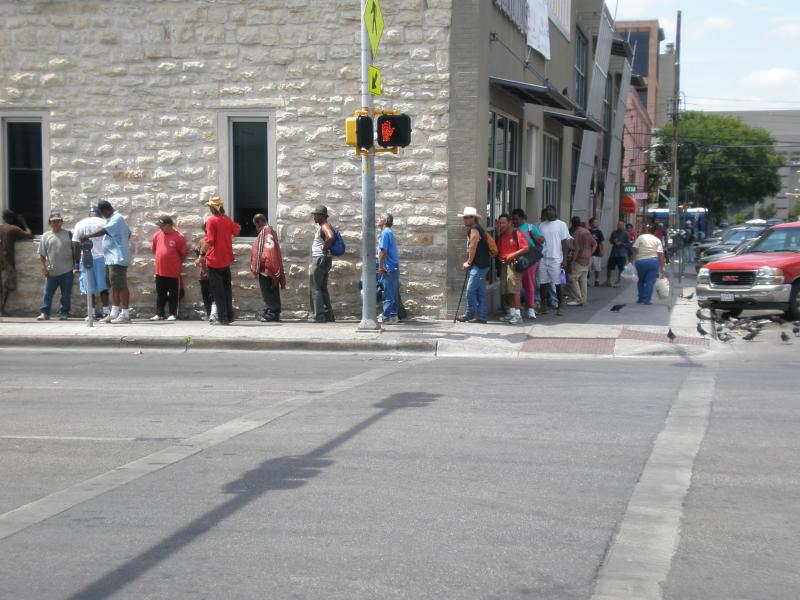 """House the Homeless"" is trying to round up hats with tails that drape down over the neck and ears to help homeless people, like these lined up outside Caritas in Austin, defend themselves against 100-plus degree temperatures"