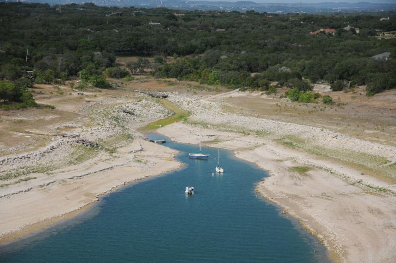 Levels in Lake Travis are at record lows. That's just one symptom of a drought that could push Austin into tighter water restrictions.