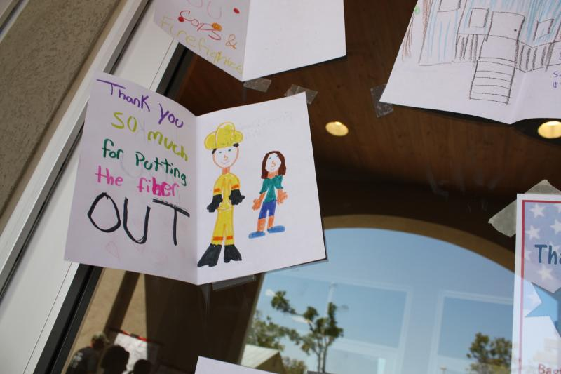 A child's piece of artwork thanking firefighters for battling the Bastrop wildfire is taped on the window at the Bastrop Convention Center.