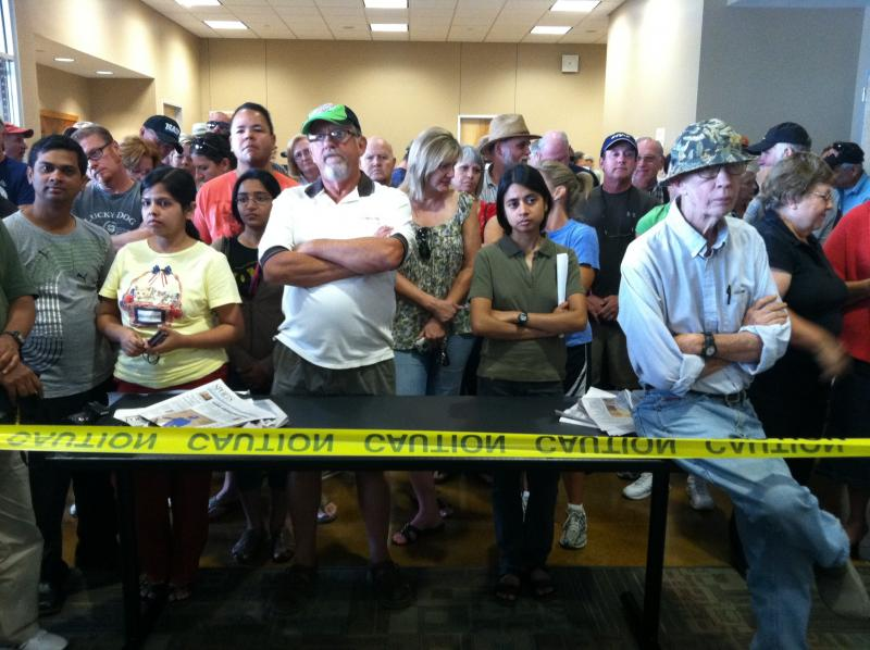 Evacuated residents wait for a briefing to begin this morning at the Bastrop Convention Center.