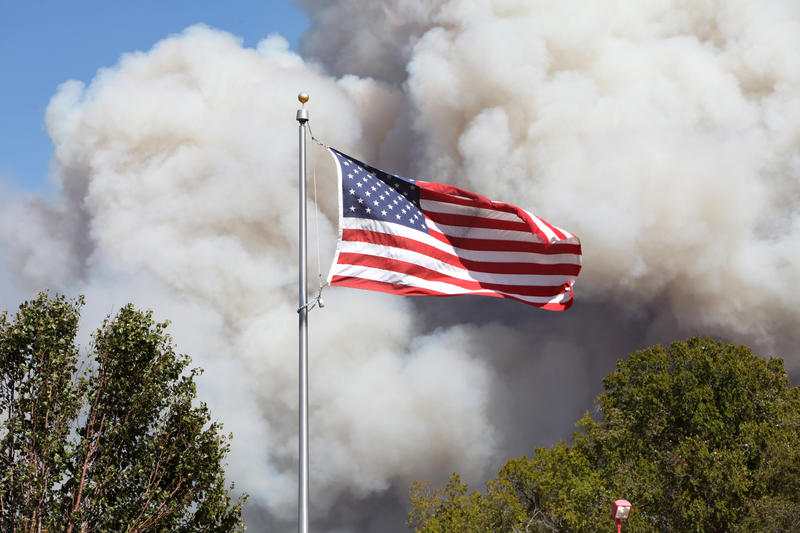 Smoke plumes billow behind an American flag near the fire in Bastrop County.