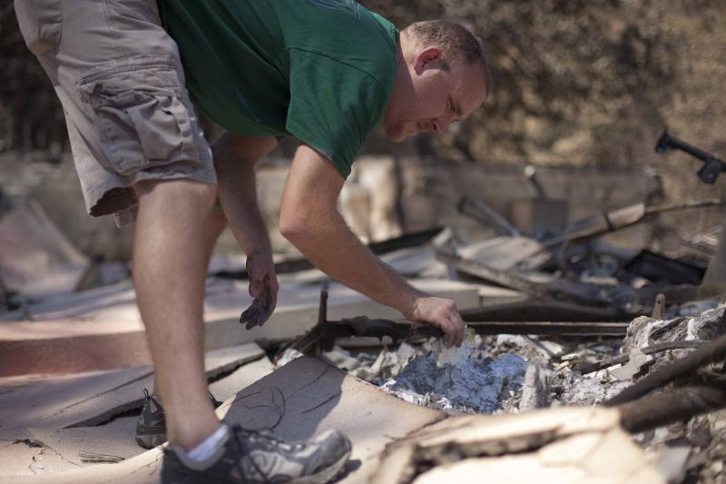 Youth pastor Robert Anderson sifts through the ashes today at Word of Life Church off US 21 in Bastrop.