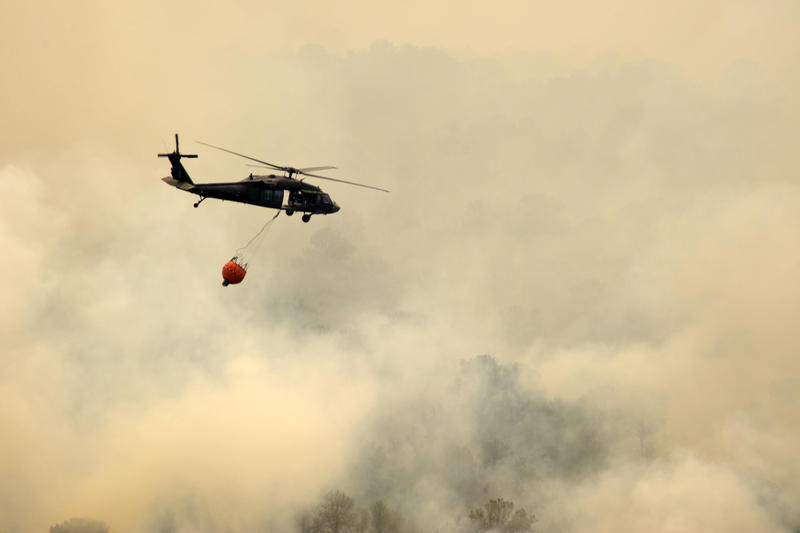 A Texas National Guard CH-46 Blackhawk flies right into the smoke to dump its water over the wildfire in Bastrop County. Smoke from the fire blanketed Austin this morning.