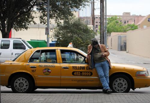 A taxi driver stretches his legs in Downtown Austin.