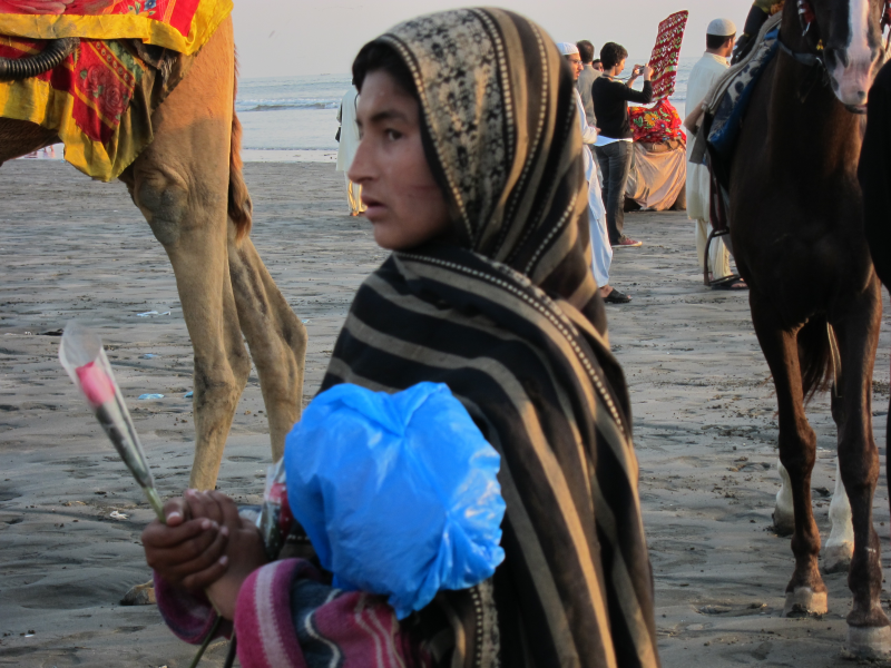This girl sells roses on the beach in Karachi, Pakistan