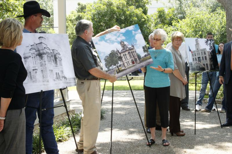 Sue Butler Carter of the Karnes County Historical Society and  Chair of the Karnes County Historical Commission Truett Lee Hunt (center) reveal what their county courthouse will look like after renovation.