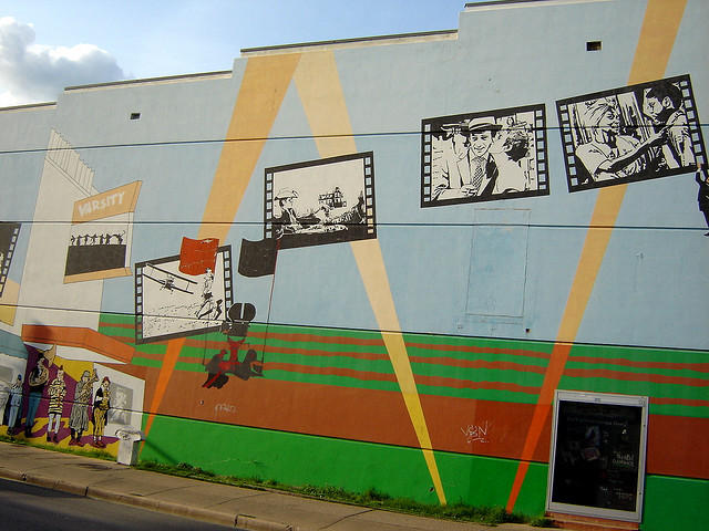 The side of the old Varsity Theater, photographed in 2007. Stores entrances dot the side of the building now, but much of the original mural  has been preserved.