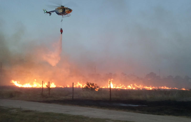 A helicopter drops flame retardant on an uncontained wildfire in Spicewood.