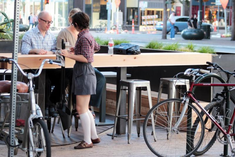 Street patios are urban design installations that convert parking spaces into café-like seating places.