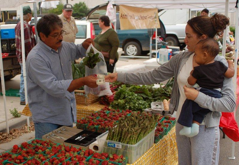 A vendor sells his wares at a local famer's market. A slew of state legislation regarding farmers markets is expected in 2013.