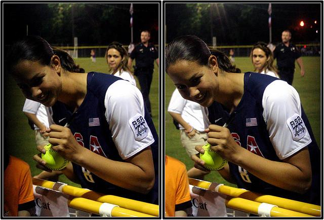 Cat Osterman signs a softball for a fan.