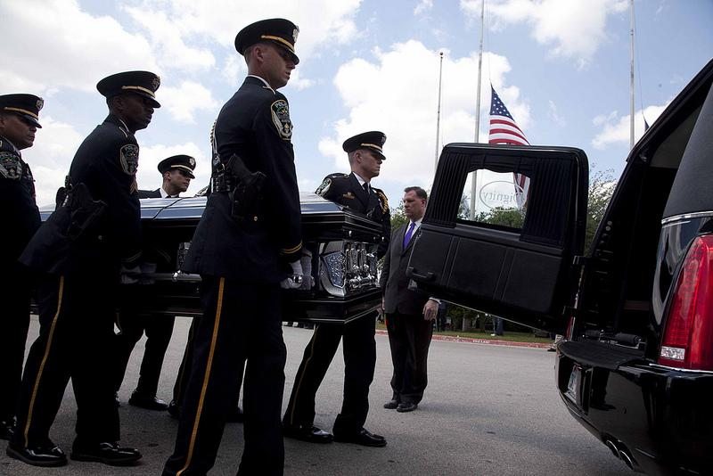 Pallbearers move Officer Jaime Padron's casket into a hearse.