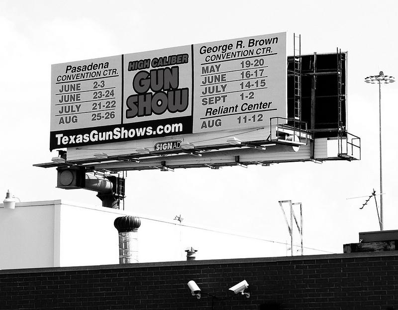 A billboard for Houston-area gun shows. Three were injured in a shooting at a Houston college campus that began as an argument.