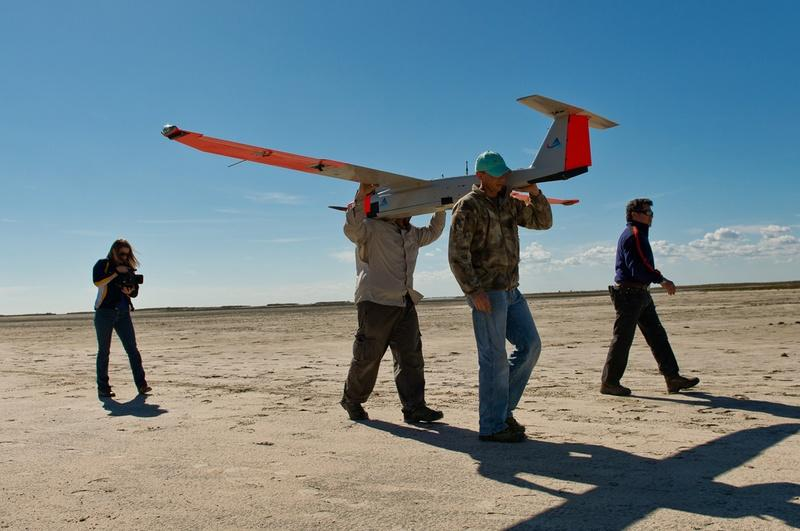 icheal Cincienne of Absolute Aerospace and Texas A&M Corpus Christi, engineering student Adam Ersepke, and lab coordinator Jack Edward Esparza carry a University drone back to the command center.