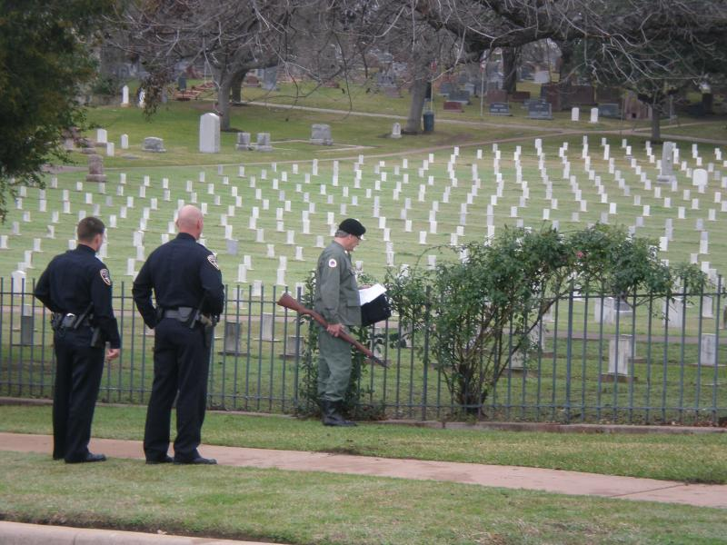 Two Austin Police officers and another man wait for Chris Kyle's funeral to begin.