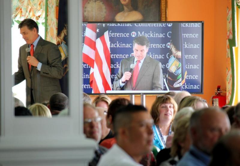 A Michigan crowd watches Gov. Rick Perry during his presidential campaign. Perry had the state pay for his security as he traveled the country campaigning.