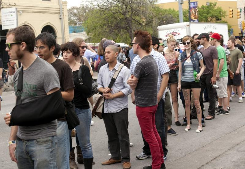 SXSW 2012 attendees lined up to get into a unofficial, RSVP-required party. RSVP services will now automatically register customers for dozens of parties.