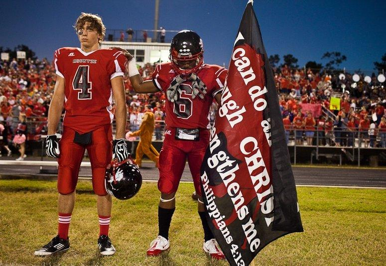 As two Kountze football players prepare to play a game on Oct. 5, 2012, one holds a banner with a Bible verse.