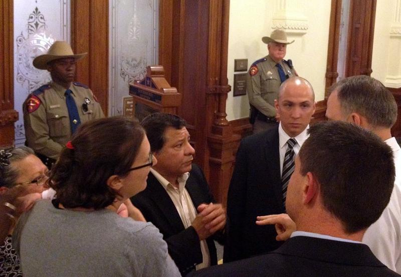 Reynaldo Gutierrez, center, was one protester who got a meeting with Gov. Perry earlier today.