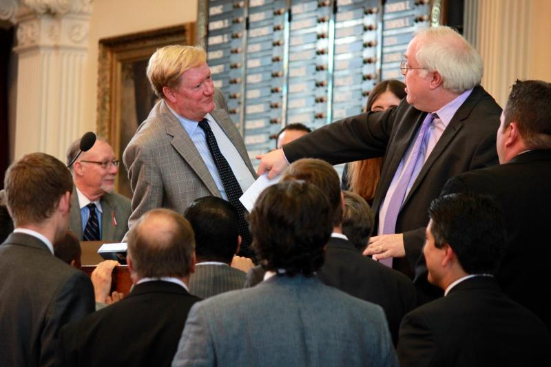 State Rep. Jim Pitts, chief budget writer in the House, left, and House Parliamentarian Chris Griesel, right, are surrounded by House members during discussion over a budget-related measure on May 25, 2013.