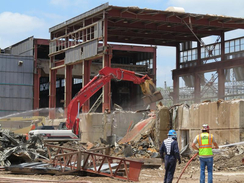 Crews tear down a building housing a turbine generator at the Holly Street Power Plant.