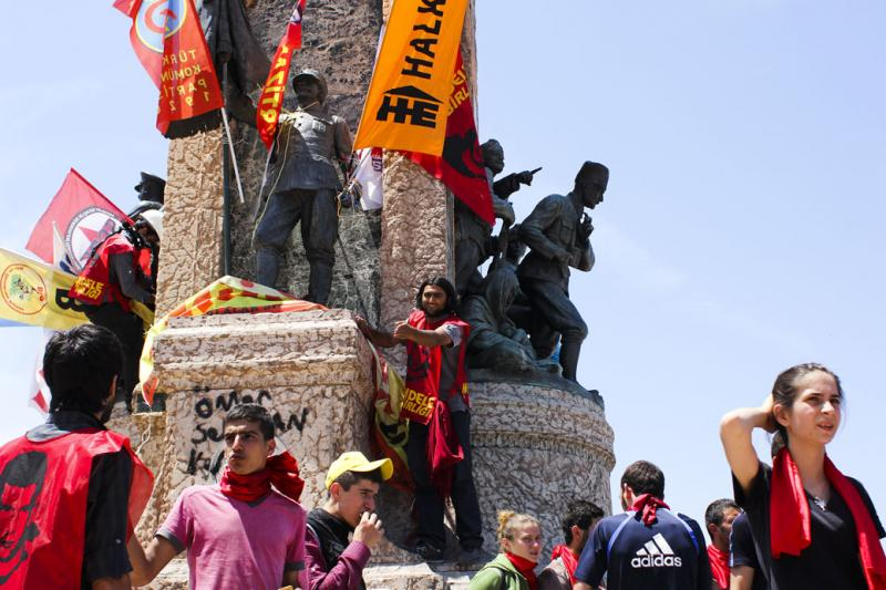 Protesters at Taksim Square climb over the Republic Statue, adorning it with flags. The flags represent organizations that stand against the current regime, including opposing political parties, universities and nonprofits.