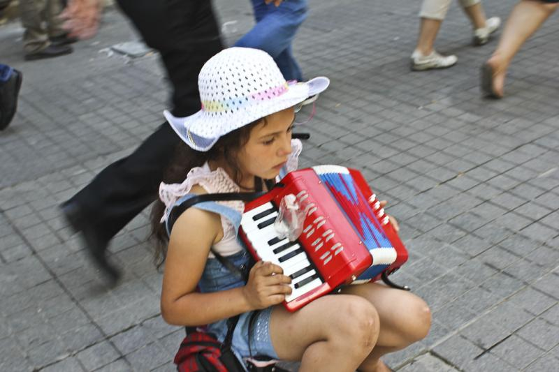 Even as people scatter from Taksim Square after tear-gas bombs shudder throughout the city center, others, like this little girl, continue to busk for their food, unphased by the protests.