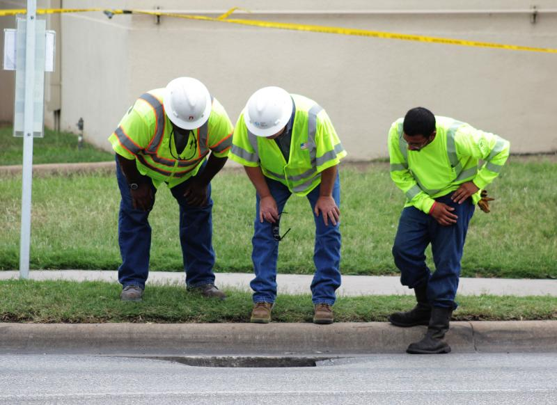 Crews inspect the sinkhole near the corner of Cesar Chavez and Sabine Streets.
