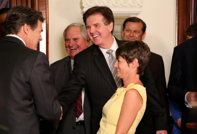 Gov. Rick Perry shakes hands with Senate Education Chair Dan Patrick as State Rep. Jimmie Don Aycock, author of House Bill 5, laughs in the center on June 10, 2013.