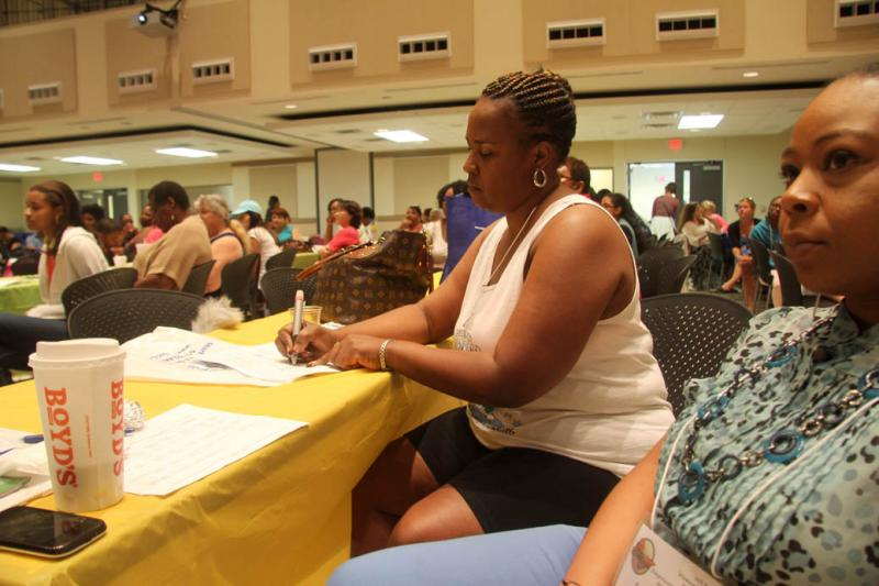 Fawn Jackson takes notes during the introductory speeches at the Women's Health, Motivation & Empowerment Conference. Jackson planned to attend the health workshops offered at the meeting.