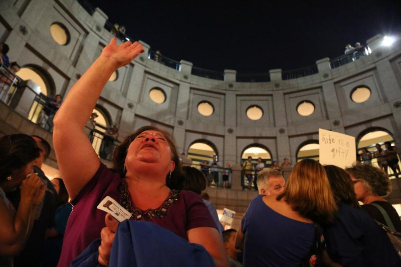 A woman prays outside as a House committee takes up House Bill 2 on July 2, 2013.