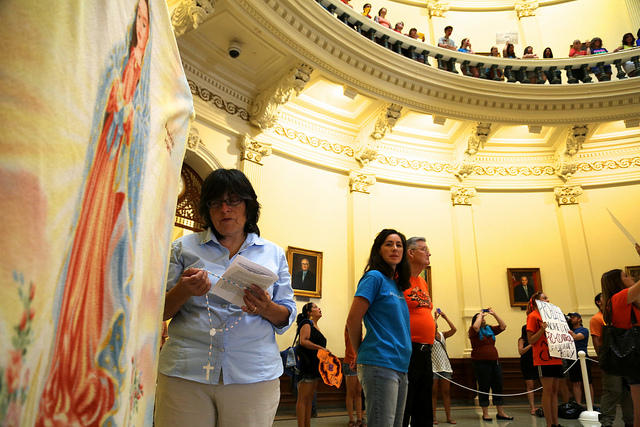 Vicky Whynott of Houston prays near a tapestry showing the Virgin Mary as Anna Meadows of Austin, wearing blue, looks on in the rotunda of the Texas Capitol on July 1, 2013.