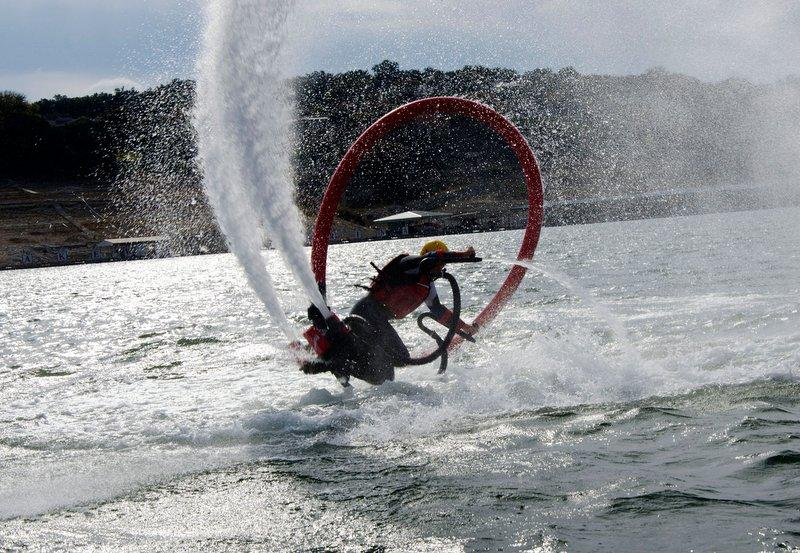 An unnamed Flyboarder finishes a backflip. Flyboarders can soar up to 30 feet above water.