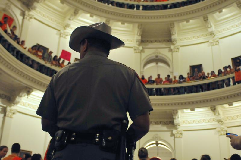 A Department of Public Safety Officer stands guard restricting entrance to the Capitol Rotunda floor as midnight approaches and hundreds of demonstrators remain inside the Capitol building.