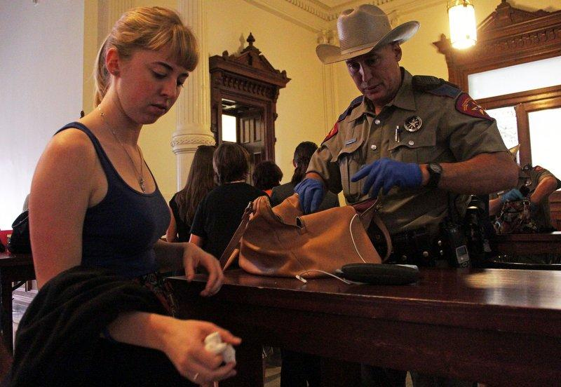 An unidentified woman has her bag searched by a DPS officer outside the Senate chambers. Those looking to get inside the gallery had tampons, along with