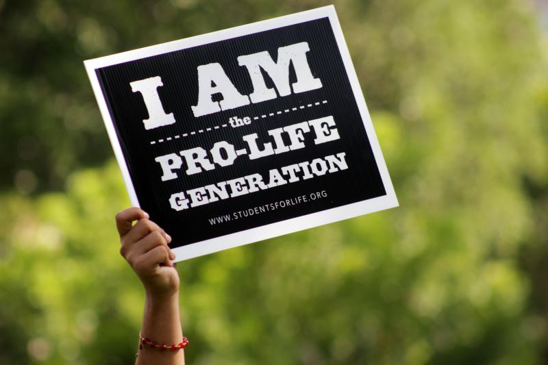 A anti-abortion protester stands outside Planned Parenthood's announcement on July 9, 2013.