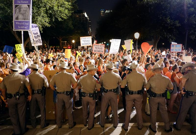 A line of state troopers blocks hundreds of protestors (primarily abortion-rights advocates) from the Capitol steps as an anti-abortion rally comes to a close Monday.
