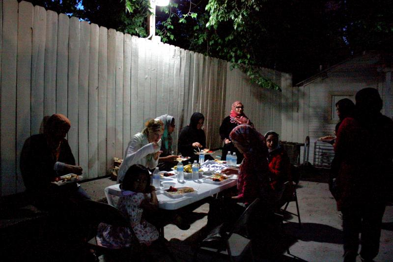 Women sit down to eat after mosque volunteers serve dinner, cafeteria-style.